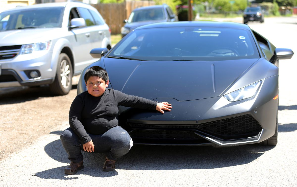 Adrian Zamarripa poses in front ofJeremy Neves' Lamborghini Huracan as his family to take photos in Ogden on Tuesday, May 5, 2020. Adrian, who is 5, tried to drive his parents' car to California to get his own Lamborghini on Monday, He was stopped by the Utah Highway Patrol just a few miles from his home.