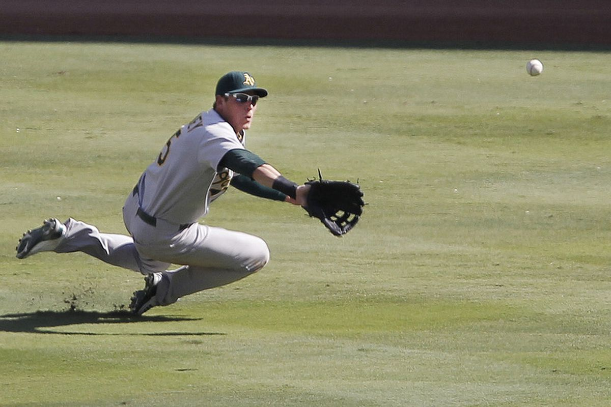Ryan Sweeney, formerly of the Oakland Athletics, catches a fly ball during the fourth inning at Rangers Ballpark in Arlington in Arlington, Texas. Oakland won 8-7. (Photo by Brandon Wade/Getty Images)