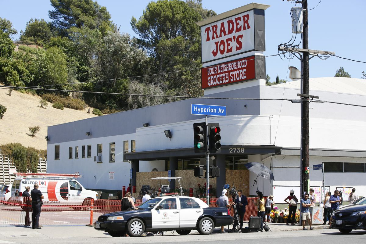 Police officers guard the entrance to the Trader Joe's Los Feliz store, as it remains closed for business, Sunday, July 22, 2018, in Los Angeles. A day earlier, Trader Joe's employee Melyda Corado was shot and killed at the store by a suspect being chased