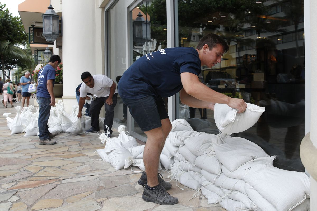 Austin Seawright, right, stacks sandbags in front of a closed store in preparation for Hurricane Lane, Thursday, Aug. 23, 2018, in Honolulu. Forecasters say Hurricane Lane has shifted course and is now moving closer to Hawaii. National Weather Service met