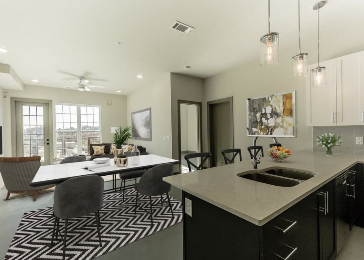 Kitchen with black cabinets, gray countertops, barstools at the counter, and a table and chairs across from the counter.
