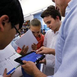 Teacher Syd Lott, right, helps students John Bergerson, left, Isabel Roberts and Max Cline during IB Economics class at Skyline High School in Salt Lake City, Tuesday, Oct. 20, 2015.
