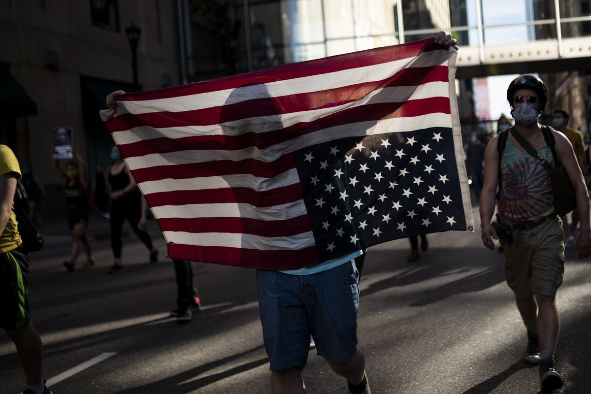 A protester holds a United States flag upside down.