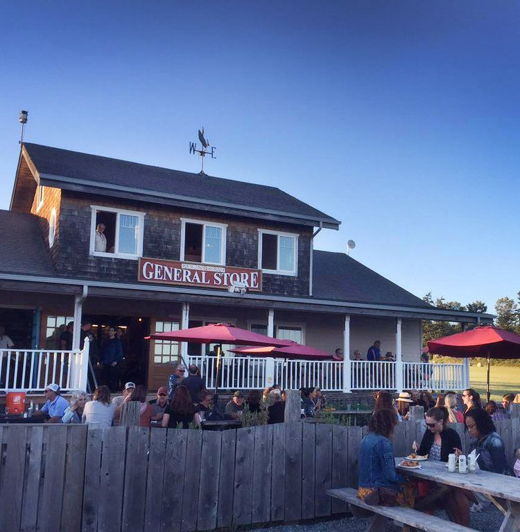 """A view of the Guemes Island General Store, a two-story building with a sign out front that says """"General Store,"""" and diners sitting on an outdoor patio"""