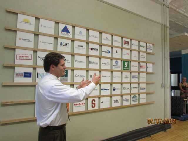 Providence Cristo Rey High School President Joe Heidt stands before a display with the names of the school's 63 corporate work-study partners. (Scott Elliott)