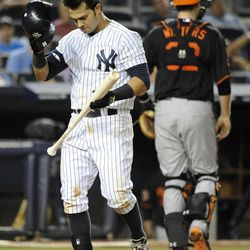 New York Yankees' Nick Swisher takes off his helmet after striking out to Baltimore Orioles relief pitcher Darren O'Day in the eighth inning of a baseball game on Friday, Aug., 31, 2012, at Yankee Stadium in New York. The Orioles won 6-1.