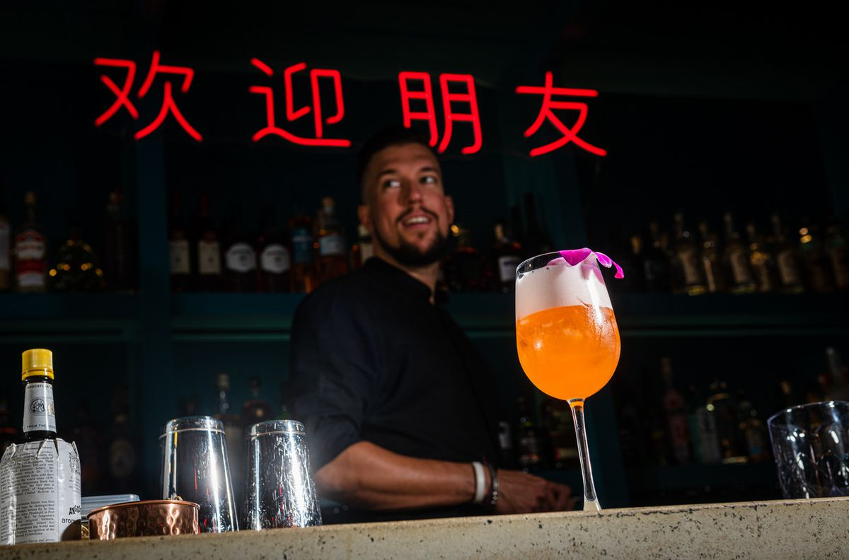 Bar manager Jacob Simpson works in front of a foamy mezcal cocktail at Bar Chinois