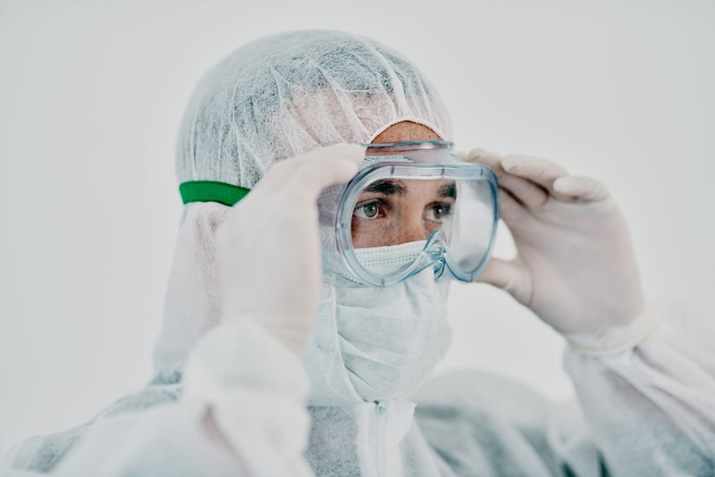 Shot of a young man putting on his protective gear before the decontamination process.