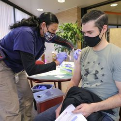 Terry Begay, a Salt Lake County Health Department advanced EMT, gives the Moderna COVID-19 vaccine to Tyler McKelvey, a Classic Air Medical dispatcher, at the Salt Lake County Government Center in Salt Lake City on Tuesday, Jan. 5, 2021.