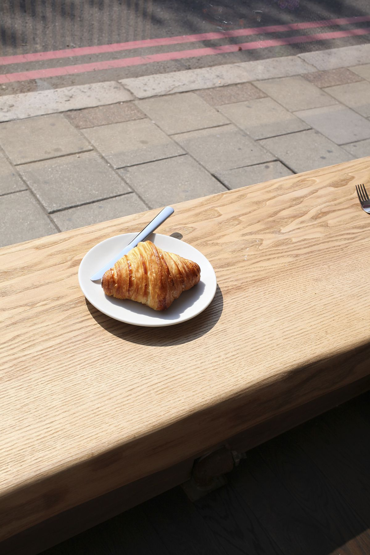 A single croissant on a white plate in the sunshine, sitting on a wooden bench, at Kapihan Battersea