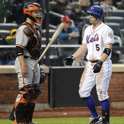 New York Mets' David Wright flips his bat in front of San Francisco Giants catcher Buster Posey after striking out to Giants relief pitcher Dan Otero in the ninth inning of the first game of a baseball doubleheader Monday, April 23, 2012, in New York.