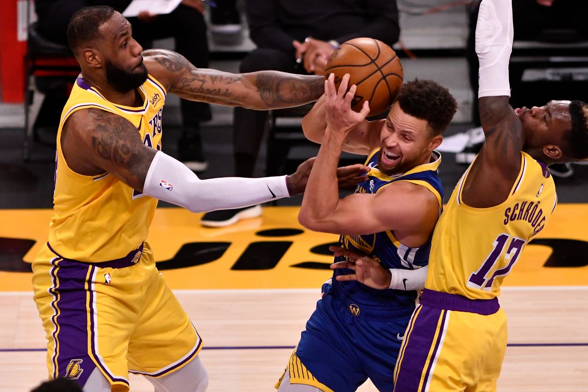 Golden State Warriors guard Stephen Curry is sandwiched between Los Angeles Lakers forward LeBron James and Los Angeles Lakers guard Dennis Schroder during the third quarter at Staples Center.