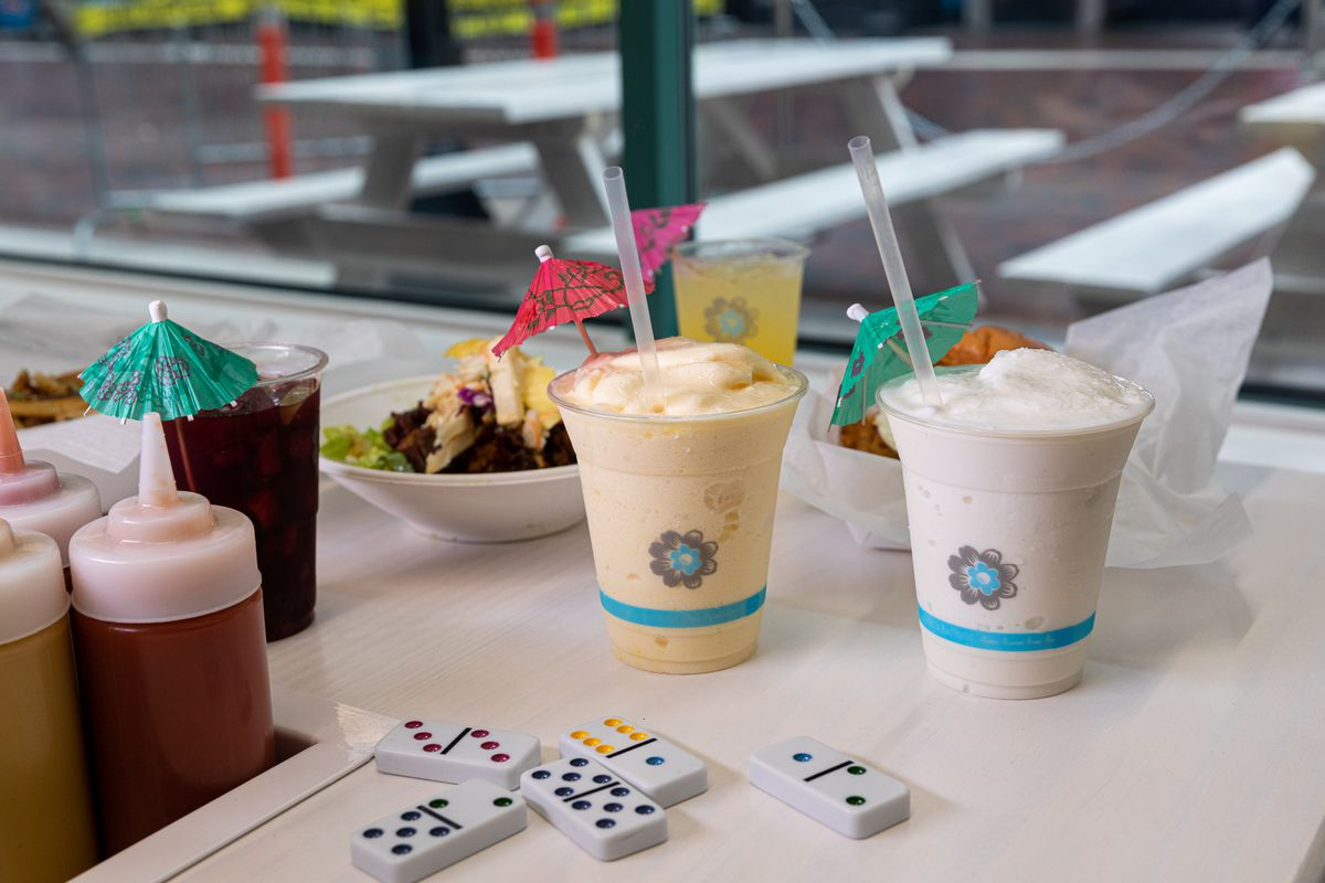 The shake are in plastic containers. The one on the left is a pale orange color with a pink umbrella and a straw, while the one on the right is white with a green umbrella.