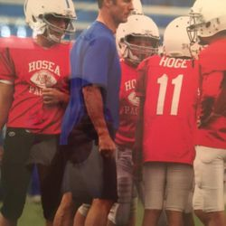 Merril Hoge coaching his son, Beau (No. 11), in youth football.