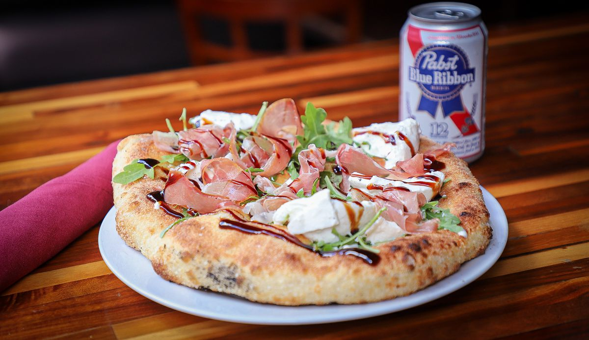 A Neopolitan pizza and can of PBR