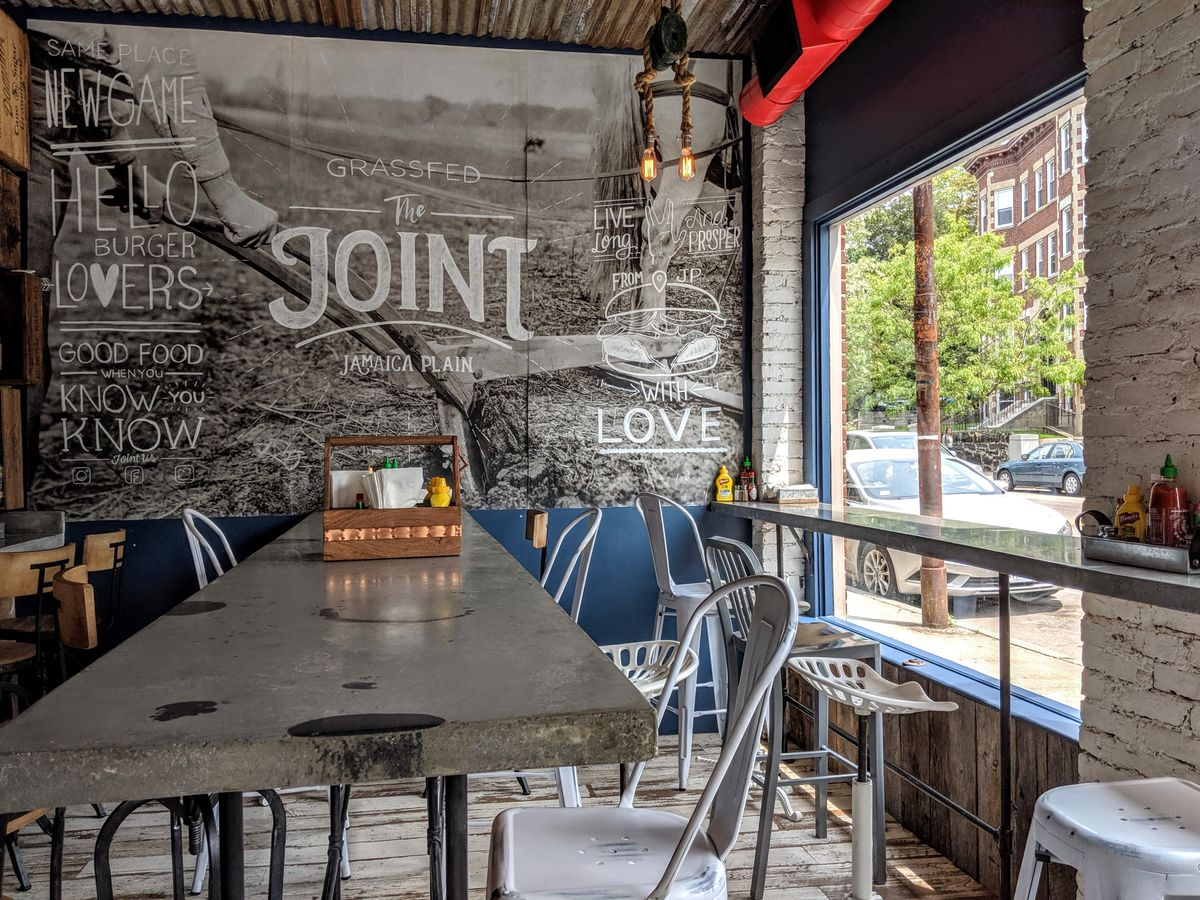 """An interior photo of the Joint, including a mural with the name of the restaurant and some other text (such as """"hello burger lovers""""), plus a high-top communal table"""