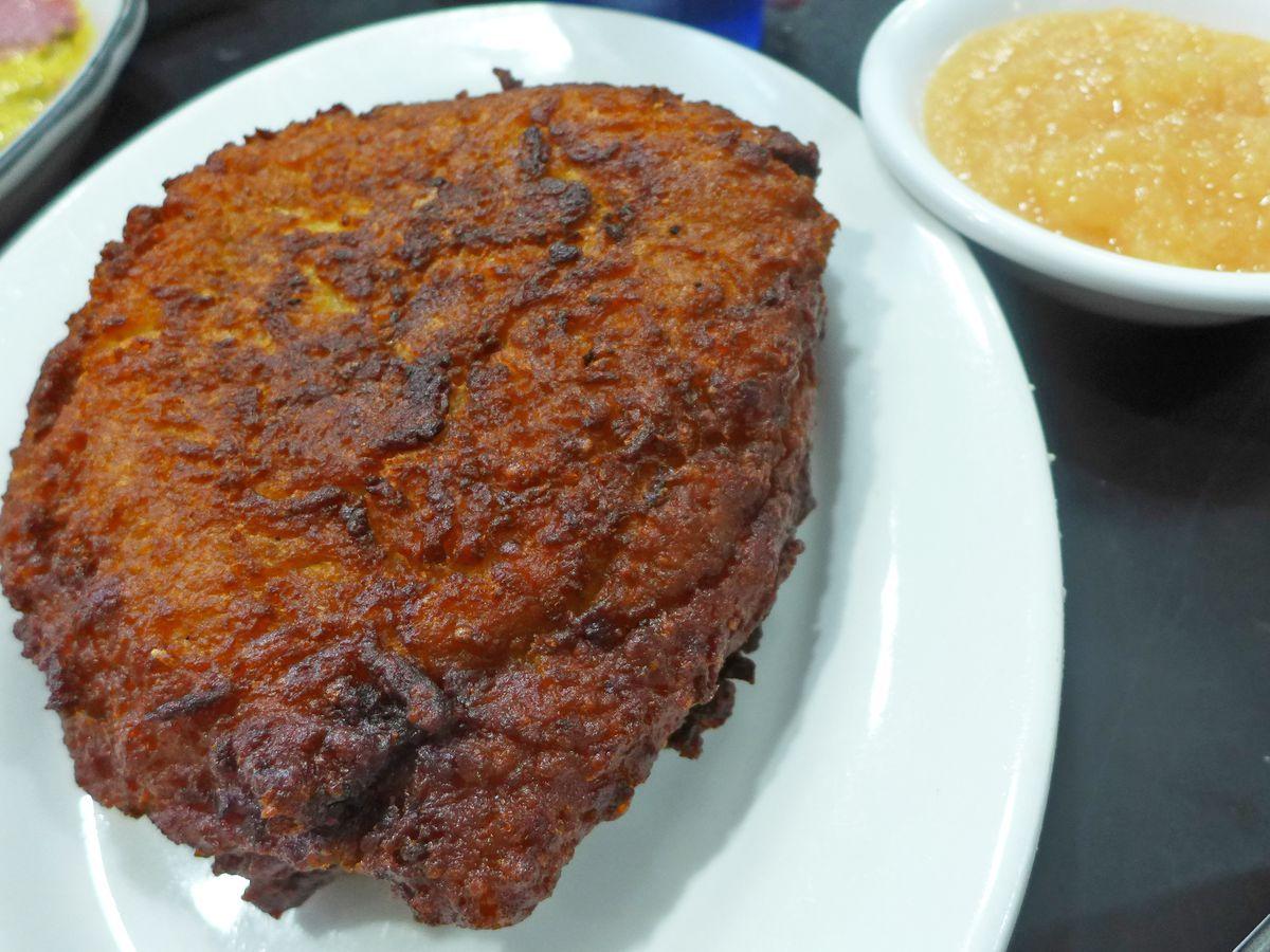A sizable potato latke takes up a whole plate, next to a side of apple sauce