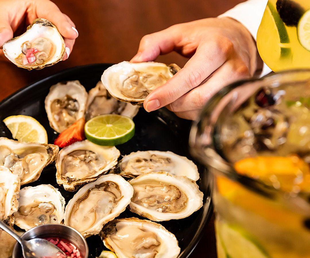 A hand picks up an oyster.