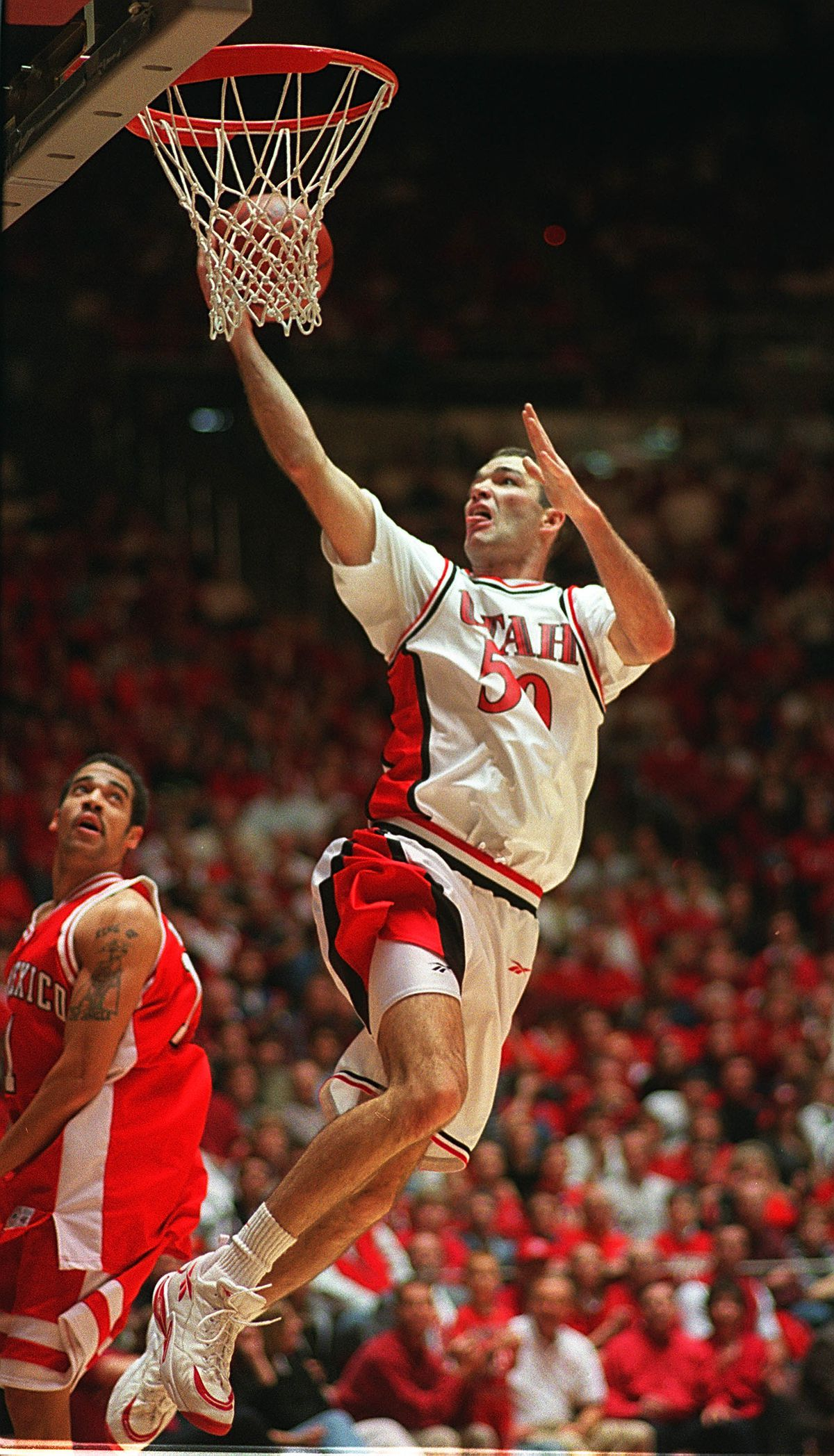 Alex Jensen scores on New Mexico's Kevin Henry in the Huntsman Center.