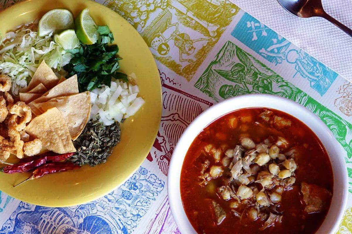 On a placemat, a bowl of pozole sits next to a plate of accompaniments like limes and onions.