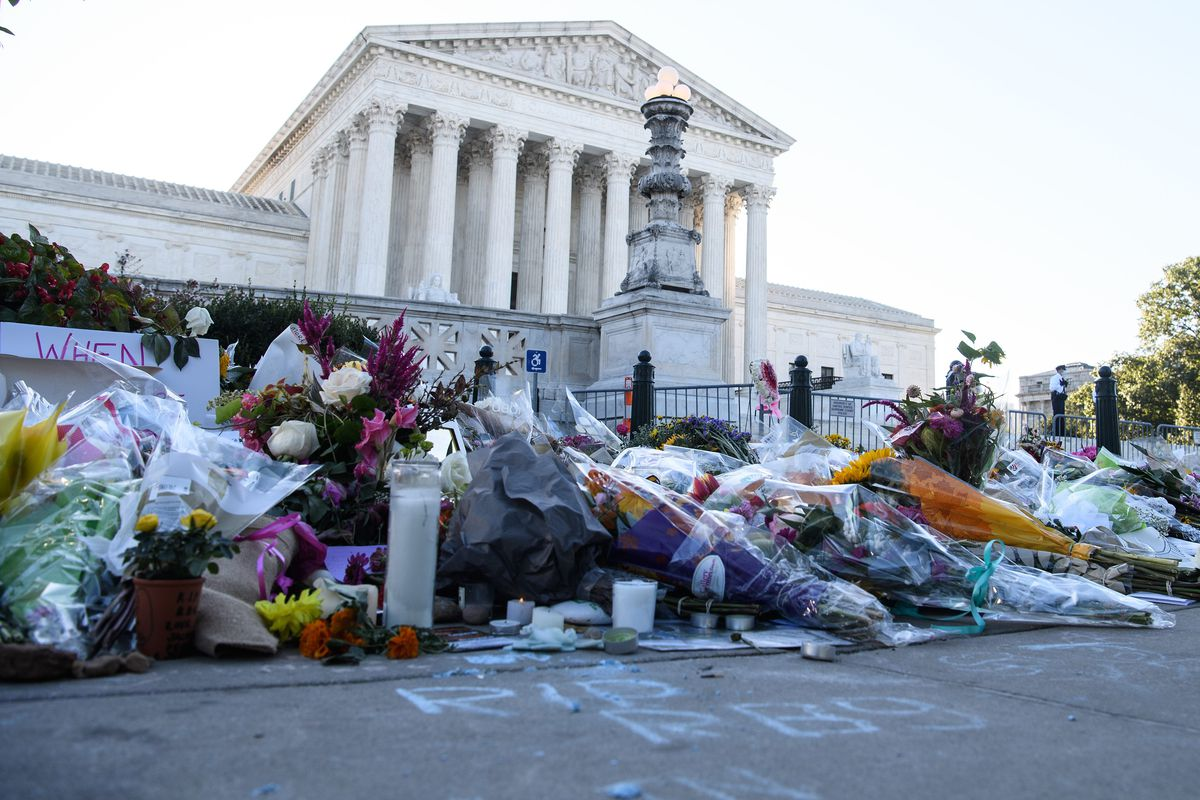 Piles of flowers, condolence cards, and candles on the pavement outside the Supreme Court building.