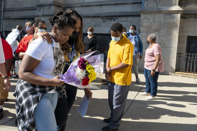 Angela Gregg, mother of slain 4-year-old Mychal Moultry Jr., is comforted as she walks back to St.  Sabina Church after a news conference about her son on Thursday, Sept. 9, 2021.