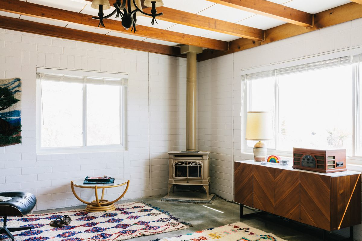 The living room has a concrete floor with several colorful, patterned rugs.