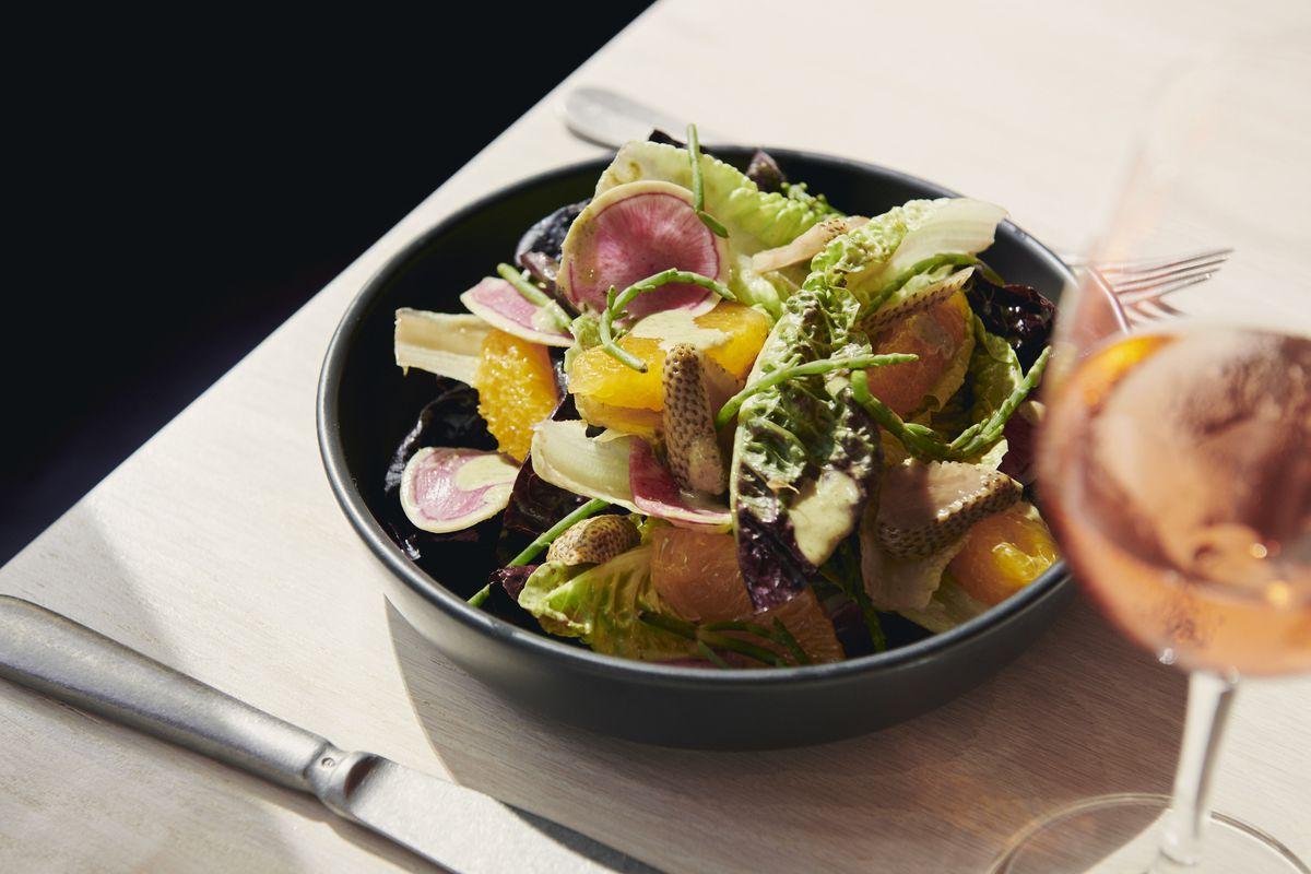 Little gem salad with tarragon vinaigrette, sea beans, watermelon radishes, orange, and pickled green strawberries