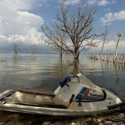 In this Sept. 5, 2012 photo, a jet ski sits parked on the shores of Lake Enriquillo in Jimani, Dominican Republic, near the border with Haiti. The waters' rise has worsened exponentially in recent years, especially after heavy rains in 2007 and 2008 hit the island of Hispaniola. Tropical Storm Isaac dumped more water on the region last month, sparking more damage.