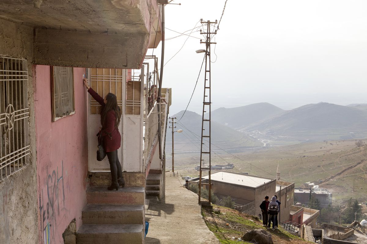 A woman reaches up in front of a door next to a pink walled house