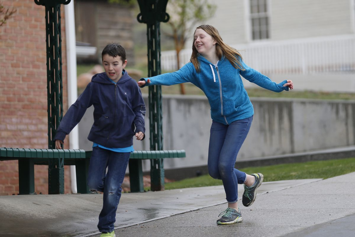 In this April 6, 2018, photo, Caleb Coulter, 10, left, and his sister Kendra, 12, play tag during a visit to the Place Heritage Park in Salt Lake City. Critics say letting children strike out on their own can expose them to serious dangers. But lawmakers