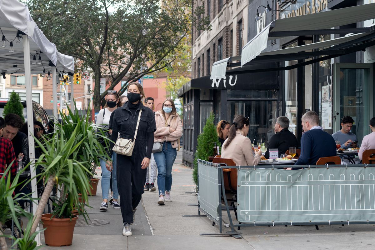 People wearing masks walk near a restaurant's outdoor dining setup in the West Village on October 18, 2020 in New York City.