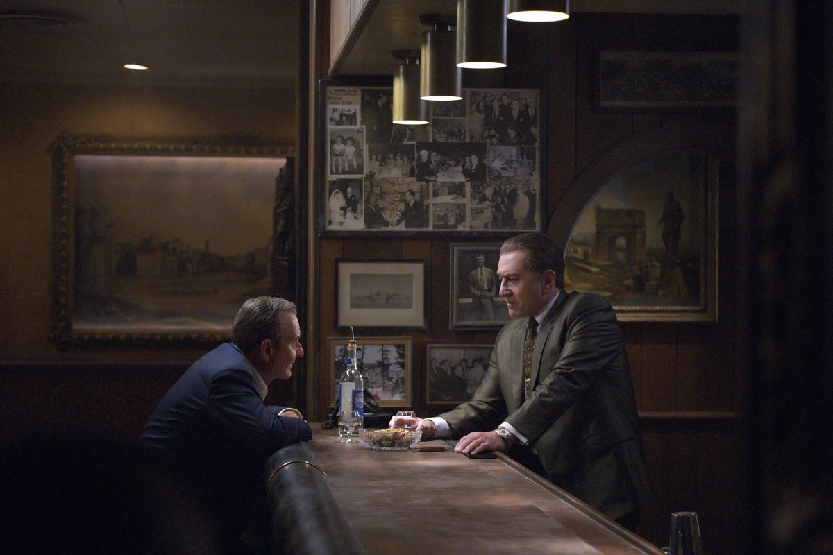 "A scene from the movie ""The Irishman"" shows Joe Pesci sitting at a bar and Robert De Niro standing behind the bar."