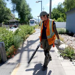 Piper Caldwell cleans up the walkway along the S-Line tracks in Salt Lake City on Tuesday, June 27, 2017.