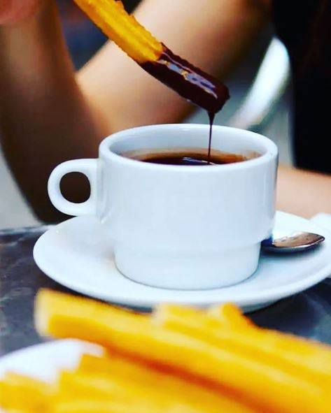 A churro drips chocolate into a cup right after being dipped.