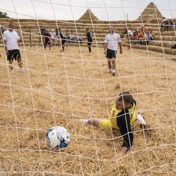 """In this photo taken on Saturday, June 4, 2016, people ply football at the arena, made of 4,500 straw bales, comes complete with tiered seating and flagpoles in Krasnoye, Stavropol region, South Russia. In a project straight out of the """"Three Little Pigs"""" fairytale, Roman Ponomarev has built a straw replica of the 643-billion-ruble ($700 million) stadium in St. Petersburg which will host World Cup semifinals. (AP Photo/Oleksandr Stashevskyi) ORG XMIT: XAZ127"""