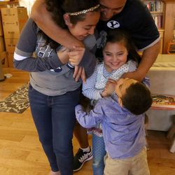 Kalani Sitake hugs his children Skye, 11, Sadie, 8, and KK, 5, at home in Provo on Friday, March 11, 2016.