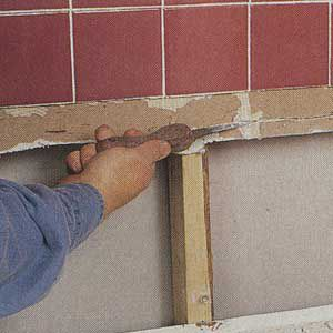 <p>TRIM THE BROKEN edge of the existing gypsum wallboard with a drywall saw to create a neat, straight horizontal seam.</p>