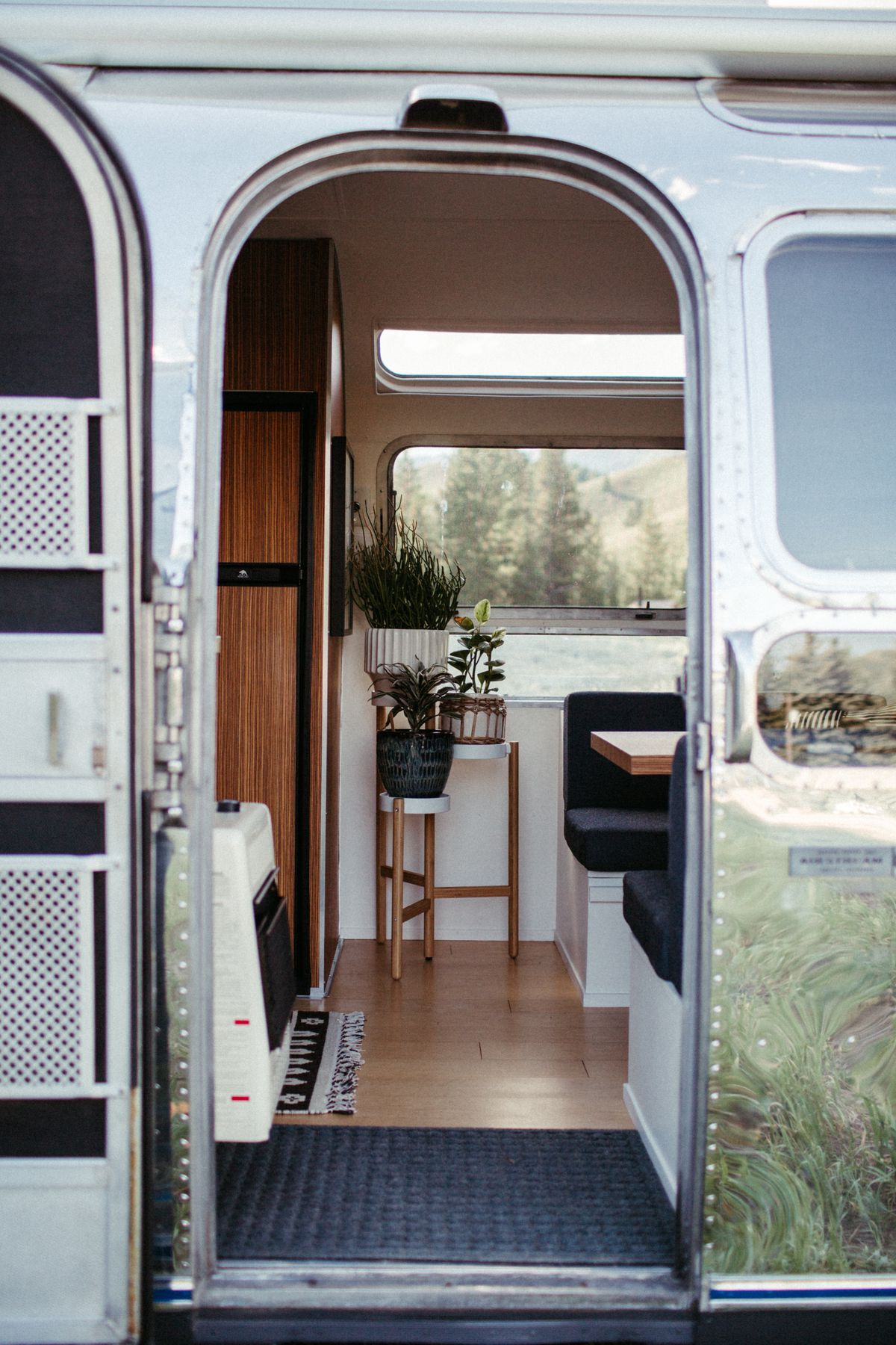 A door of an Airstream trailer is open and you can see plants and a dinette inside.
