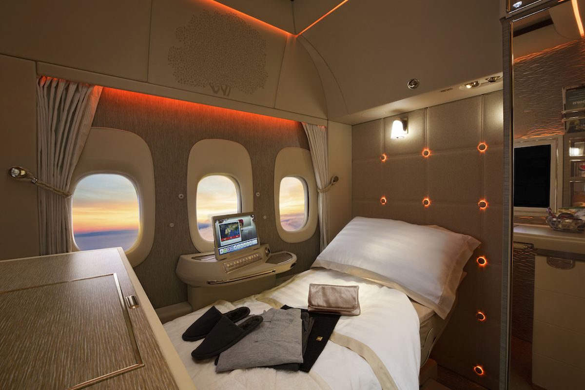 View of airline cabin with three windows and a reclining seat with a pillow and sheets.