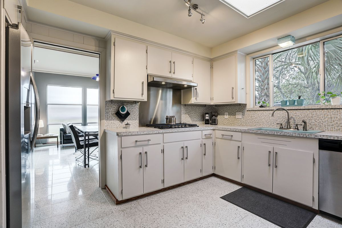 A kitchen has white cabinets, light gray counters, and a large window over the sink.