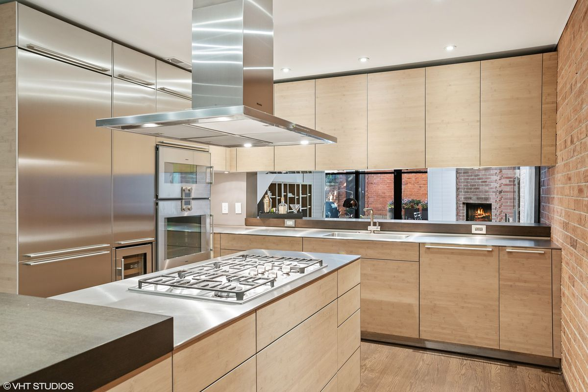 There is a concrete island, stainless steel range, and wooden cabinets.
