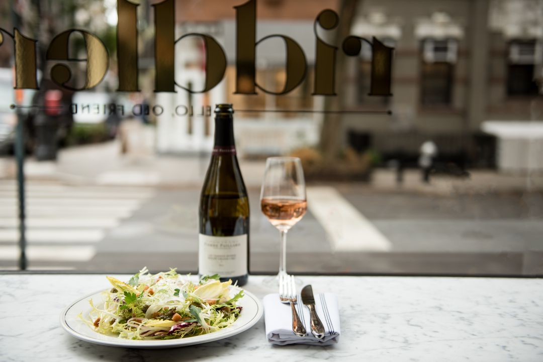 A frisee salad with a bottle and glass of wine in front of a window