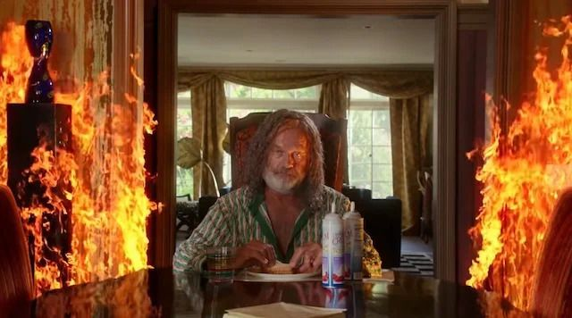 Kelsey Grammer sits at the far end of a kitchen table eating a sandwich as roaring flames rage around him.