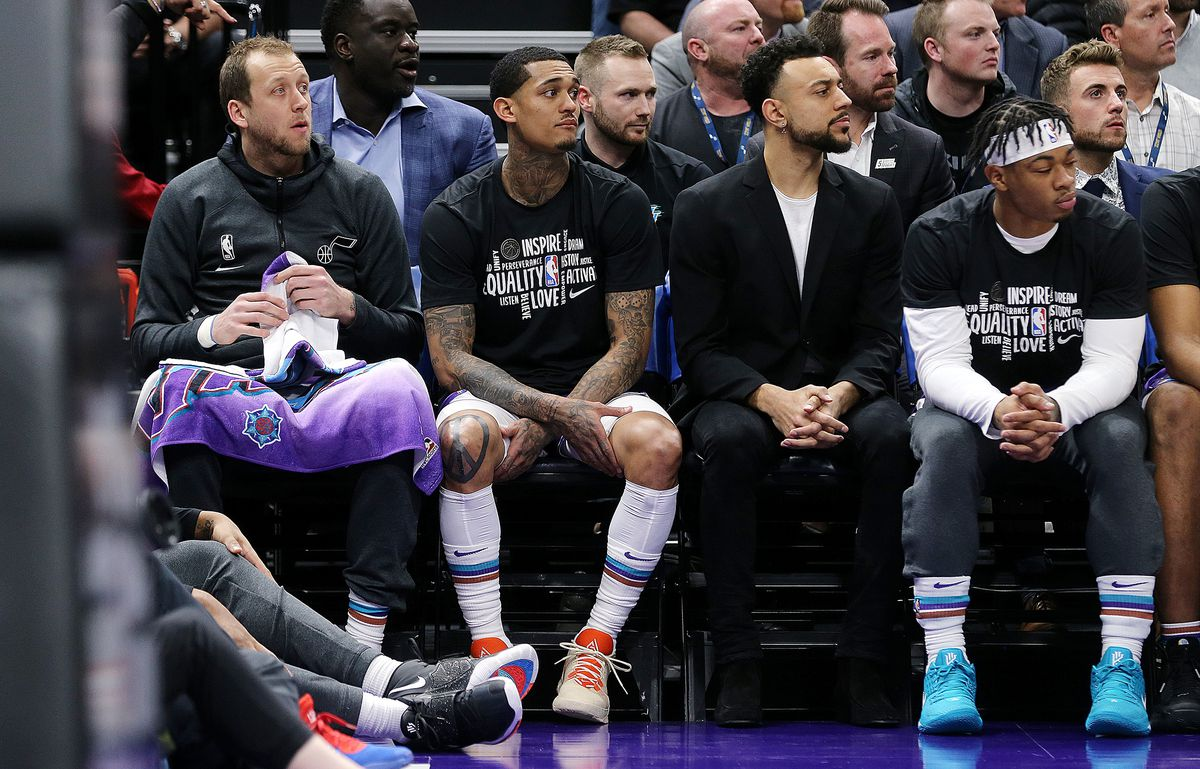 Utah Jazz guard Joe Ingles (2), left, sits on the bench to start the game as the Utah Jazz and the Boston Celtics play an NBA basketball game at Vivint Arena in Salt Lake City on Wednesday, Feb. 26, 2020.