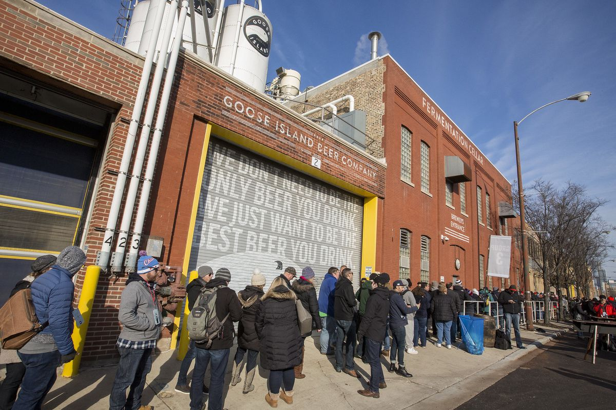 A group of folks wearing wintry coats and gear waiting outside a brewery.