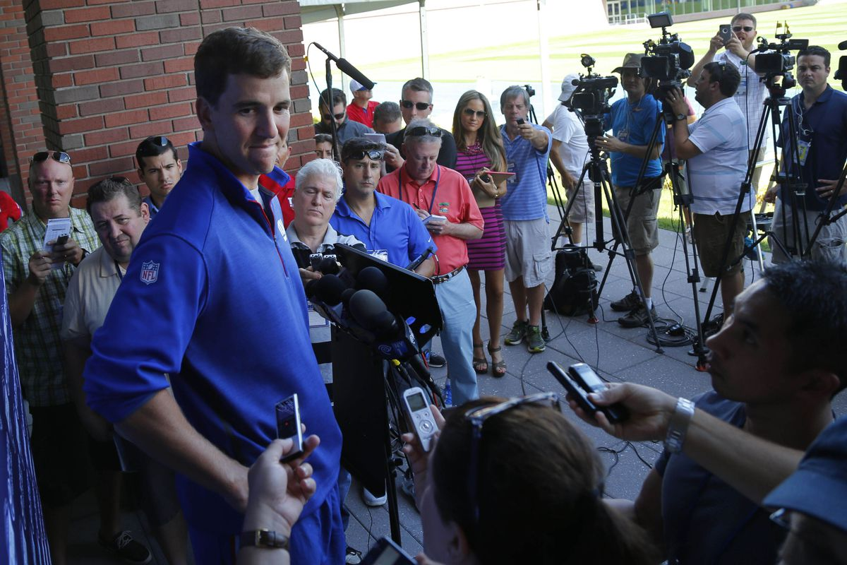 Eli Manning surrounded by reporters