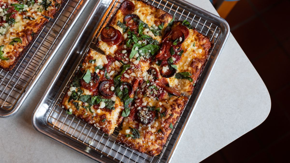 A square pizza sits on a rack over a metal pan. It's topped with thick-cut pepperoni, basil, and cheese.