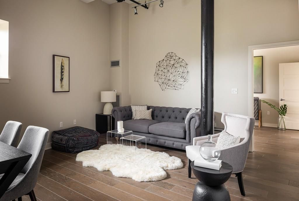 A small living room with very high ceilings, a couch, and a thin column.