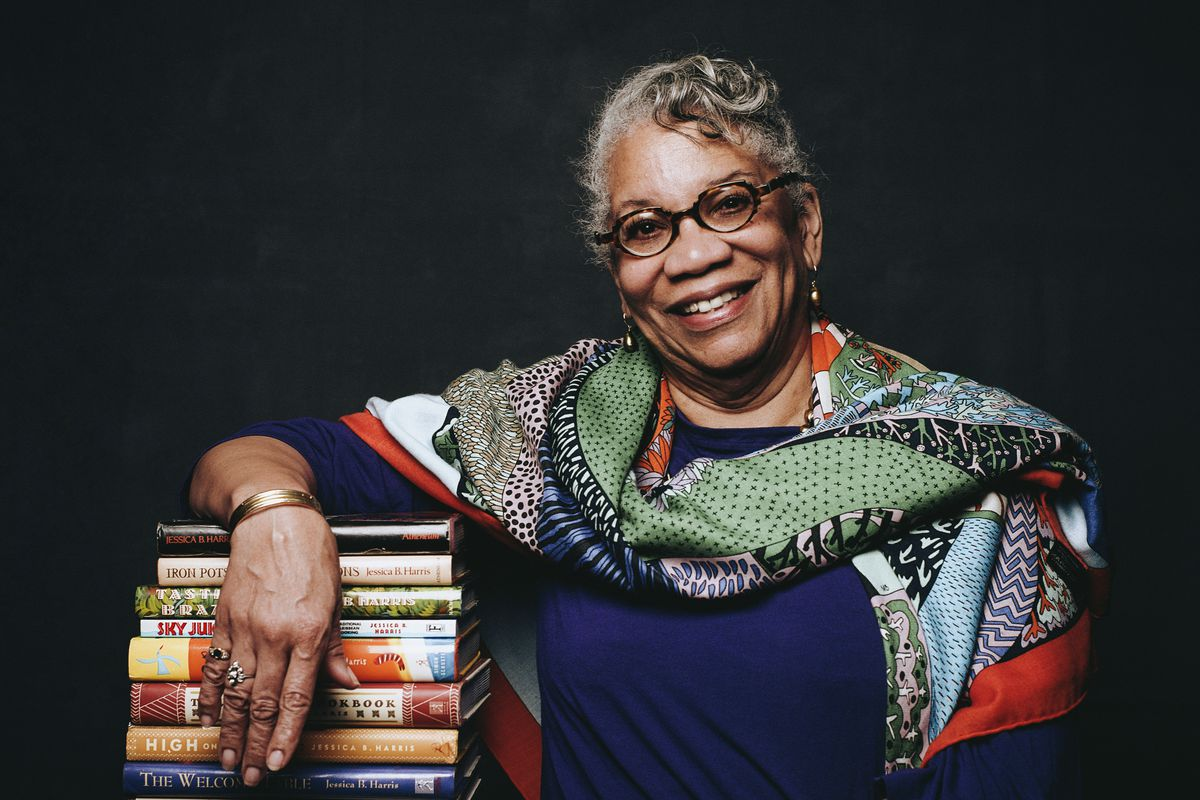 Jessica B. Harris sits with her arm draped over a stack of books.